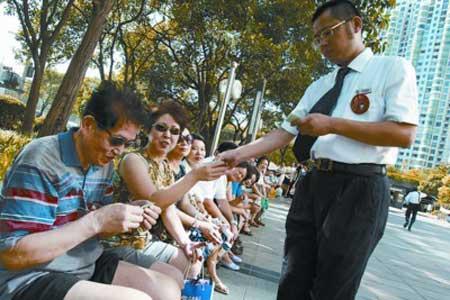 中国银行黄浦支行的工作人员给排队等待的市民发放兑换号码