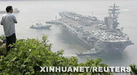 """7月14日,一男子在韩国南部港口釜山观看美军核动力航空母舰""""罗纳德·里根""""号驶进港口。当日,""""罗纳德·里根""""号抵达釜山开始对韩国的访问。 新华社/路透"""