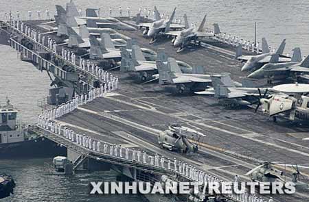 """7月14日,美军核动力航空母舰""""罗纳德·里根""""号抵达韩国釜山的海军基地后,士兵在甲板上列队。当日,""""罗纳德·里根""""号抵达釜山开始对韩国的访问。 新华社/路透"""