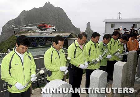"""7月14日,韩国政府官员在独岛(日本称""""竹岛"""")的纪念碑前为在捍卫独岛战斗中死去的人献花。新华社/路透"""
