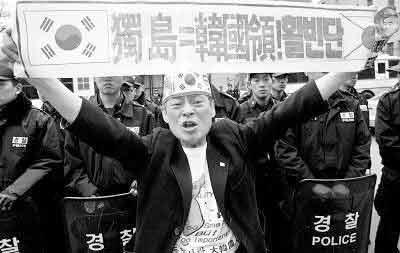 7月14日,韩国政府官员在独岛为在捍卫独岛战斗中死去的人修建的纪念碑前高喊口号