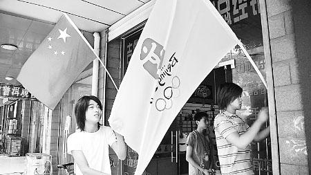 7月14日,开封市一家商店的员工正在将五星红旗和奥运五环旗插在门前。随着奥运会的临近,古城开封市大街小巷处处洋溢着喜迎奥运的气氛。⑧3                                                                                      李俊生   摄