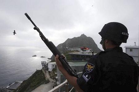 7月14日,一名韩国士兵在独岛(日本称竹岛)站岗。日本在新教科书指导纲要中记述该岛主权已引爆了日韩近年来最严重的外交风波。 新华/路透