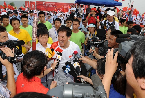 7月17日,火炬手赵本山手持火炬进行传递。当日,北京奥运圣火在沈阳市传递。 新华社记者李刚摄