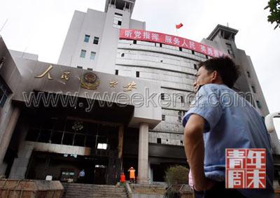 6月28日,贵州瓮安,一警察望着被烧毁的公安大楼  ◎供图/IC