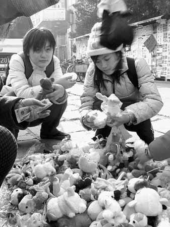 一商贩正在向大学生推销毛绒卡通玩具。现在毛绒玩具主要消费群已经明显由儿童或青少年转向成人群体,他们购买后有的作为礼品,有的根本就是出于兴趣抱回家当做装饰。尹栋逊摄