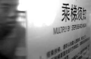 """指示牌上写着汉字""""乘梯须知"""",下方配有英文注释""""MULTIPLY BY STEPS BEARD KNOW"""" 本报记者 吴小川摄"""