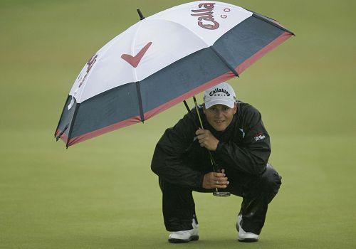 图文:英国公开赛第二日比赛 法斯躲伞下很搞笑