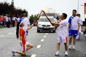 图文:奥运圣火在大连传递 火炬手单膝跪地交接