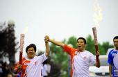 图文:奥运圣火在大连传递 火炬手激情交接