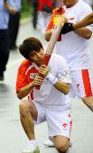 图文:奥运圣火在大连传递 火炬手跪吻祥云