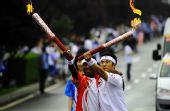 图文:奥运圣火大连传递 火炬手摆V字造型交接