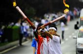 图文:奥运圣火在大连传递 孙利马可展示火炬