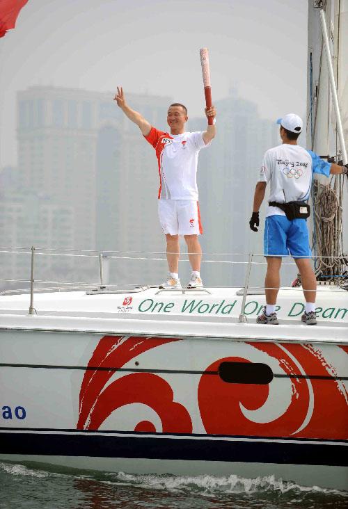 火炬手刘卫手持火炬在帆船上进行海上传递