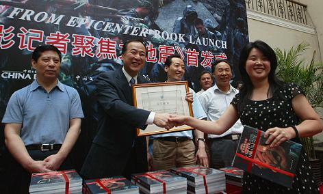中国日报总编辑朱灵(中)向国家图书馆代表赠书,国家图书馆将永久性收藏画册。左为北京市公安交通管理局局长宋建国、右为中国记协党组书记、书记处书记翟惠生。