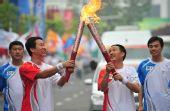 图文:奥运圣火在青岛传递 许振超与潘强交接