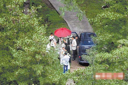 新娘子下车时,亲友依香港习俗为嘉玲撑起大红伞