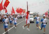 图文:奥运圣火在山东临沂传递 火炬手激情一跃
