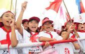 图文:奥运圣火在曲阜传递 小学生在为传递加油