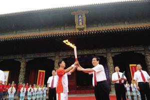 第一棒火炬手孔鹏(左)在大成殿前接过火炬