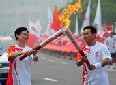 图文:奥运圣火在郑州传递 王一硕与杨玲交接