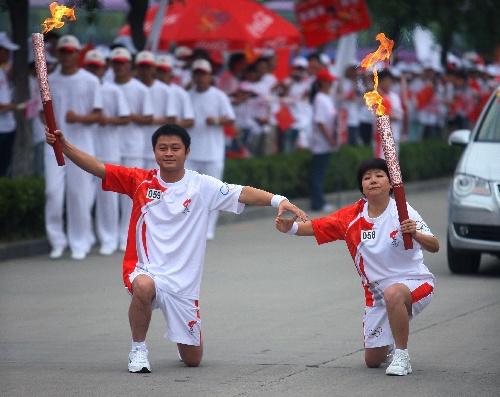 火炬手张建淑(右)与下一棒火炬手张伟交接后合影