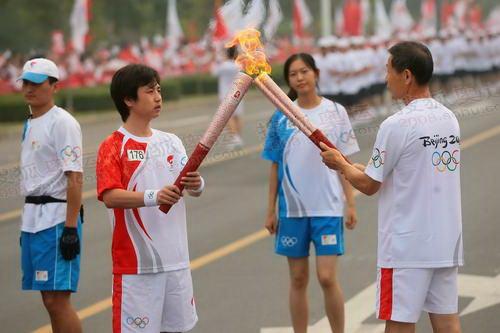 洛阳176号联想火炬手陶辉交接圣火(左)