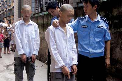 民警押着涉嫌绑架的嫌疑人指认现场