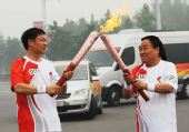 图文:奥运圣火在安阳传递 杨文周与谭荣登交接