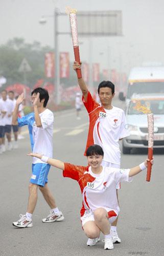 火炬手赵学恩(右后)与下一棒火炬手李蕾交接后合影