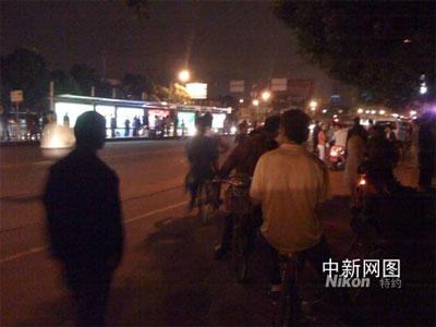 图为发生事故的现场,事故公交车被快速拖走后,还有数百名市民在围观。王林 摄