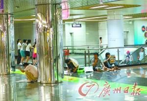 连日天气酷热,地铁出入口成了市民躲避高温的首选地。陈安 摄