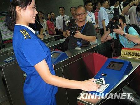 """7月17日,工作人员示范""""手机地铁票""""的使用方法。新华社记者 陈先锋 摄"""