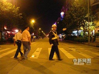 """今晚八时许,在昆明城西交林路发现一可疑黑色箱包,昆明出动大批警力将现场封锁。图为交林路与人民西路路口交警在""""断交""""。 王林 摄"""