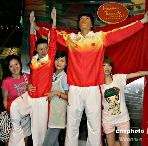 7月29日,上海杜莎夫人蜡像馆,游客与新换了装的刘翔、郭晶晶蜡像合影。该蜡像馆紧跟形势,在北京奥运会中国体育代表团领奖服公布后,新近为刘翔、郭晶晶进行了换装,立刻引来游客的好奇,纷纷驻足观看并上前与之合影留念。 中新社发 沈晨 摄