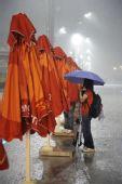 图文:奥运开幕式彩排突遇大雨 打着伞得工作者