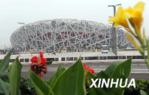 """这是7月30日拍摄的国家体育场""""鸟巢""""。当日,国家体育场""""鸟巢""""周边""""奥运花卉""""展示区景观布置工程正式完工,四季海棠、凤仙花等100多个品种的100多万盆花卉在""""鸟巢""""周边竞相开放,迎接即将开幕的北京奥运会。新华社记者沙达提摄"""