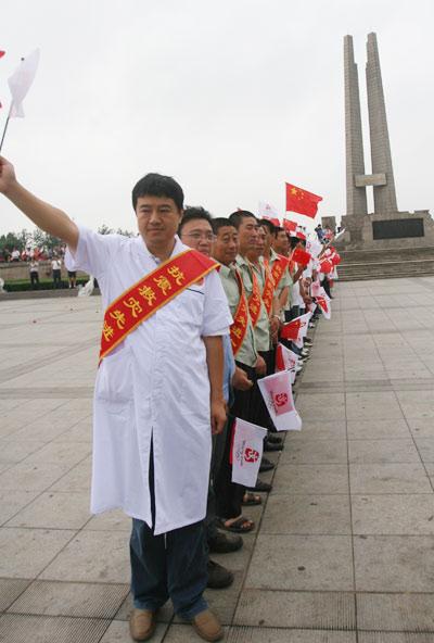 唐山抗震救灾英雄代表在抗震纪念碑喜迎圣火