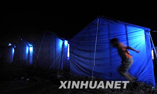 6月8日,汶川县映秀镇受灾群众安置点,一名孩子晚上在帐篷边玩耍。新华社记者 李尕 摄