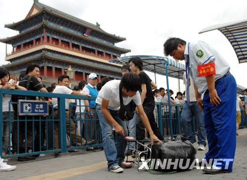 8月1日,在北京快速公交1线前门站,巡查员检查乘客行李。从当日起,北京公交车开始全面安检,2.5万名公交安保巡查员在各公交站台、车厢进行安全巡视检查。 新华社记者 金良快摄