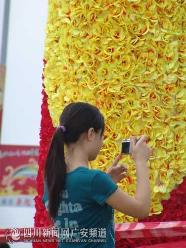 一位市民在奥运装饰花柱前专心摄影 广安频道记者易友波摄