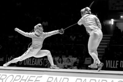 □中国著名女子佩剑运动员谭雪(左)在比赛中闪电出击