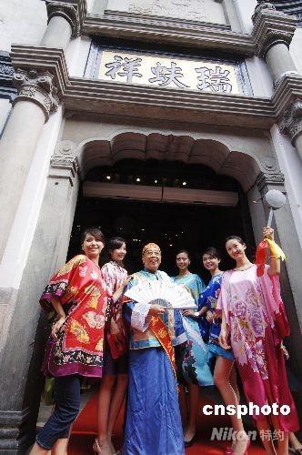 """7月30日,北京老字号""""瑞蚨祥""""重新装修开门迎客,门口叫卖大王和靓丽模特吸引路人眼球。当日,有着近500年历史的北京大栅栏商业街完成近年来最大规模改造后重张迎客。 中新社发 王东明 摄"""