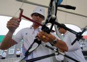 图文:韩国射箭选手备战 训练前调试弓弦