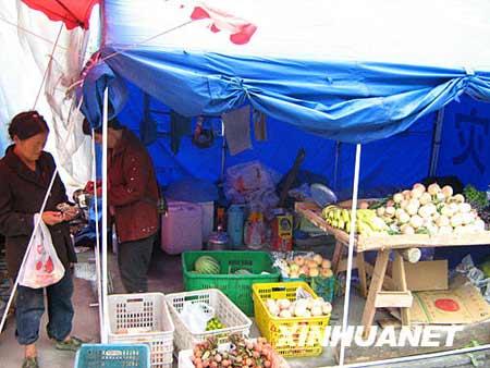 """7月12日,当地居民在四川映秀镇""""帐篷商业街""""的蔬菜水果店购买水果。 新华社记者海明威摄"""