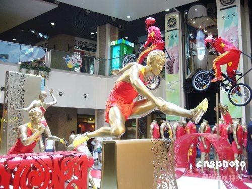 """8月3日,北京王府井东方新天地以全新的运动形象迎接奥运的到来,为王府井商业街增添了浓厚的奥运气氛。图为商场内最引人注目的""""刘翔跨栏""""。 中新社发 王宇婷 摄"""
