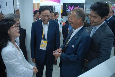 三星CEO李润雨向海博格先生介绍三星奥运旗舰手机