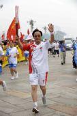 图文:奥运圣火在北京传递 火炬手刘敬民