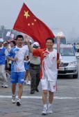 图文:奥运圣火在北京传递 肖钢手持火炬传递