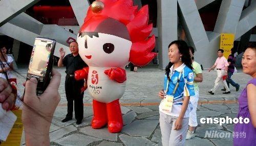 """8月5日,北京奥运会开幕式进行第三次彩排。图为彩排前,""""鸟巢""""旁的游客纷纷和""""福娃""""合影。 中新社发 王瑶 摄"""